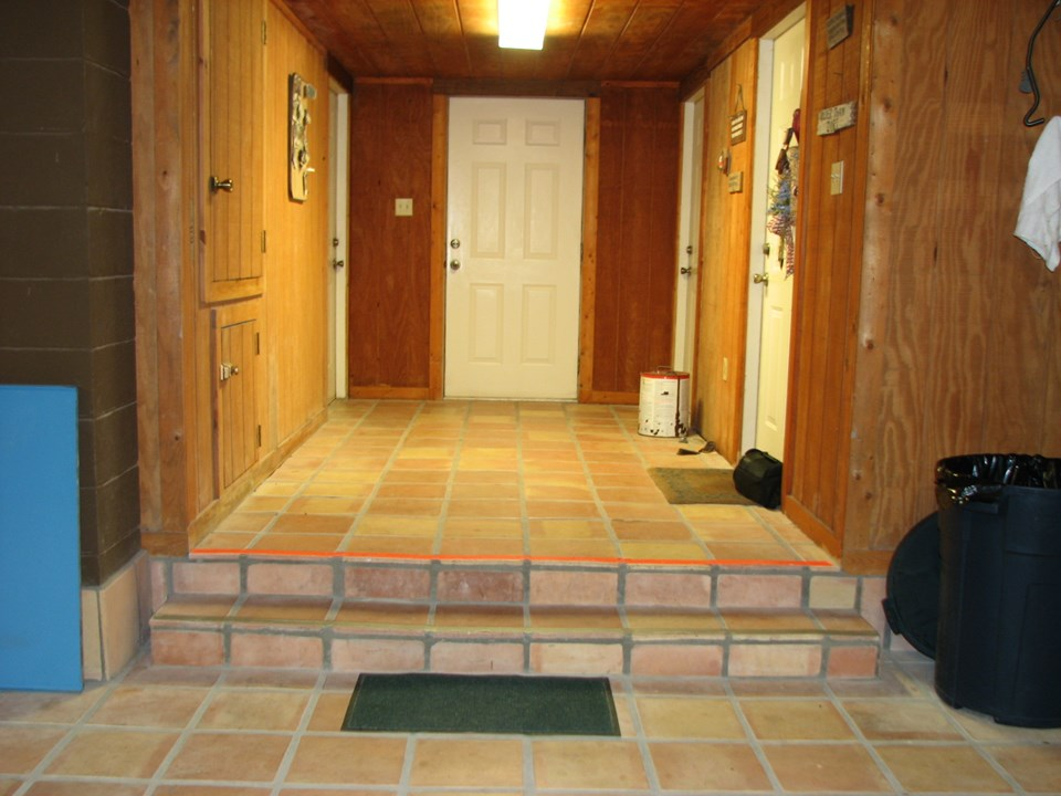 downstairs from the garage  the first door on your right is the main entry to the upstairs living areas (consisting of three bedrooms and two baths).  the second door on your right is the laundry, storage room; the door in the center background leads out to a tiled stairway for access to the boat garage, fish cleaning table and another stairway leading to the upstairs deck.  the first door on your left is a dumb waiter that goes upstairs into the kitchen area and the second door in the background on your left, is the fourth bedroom and bath.