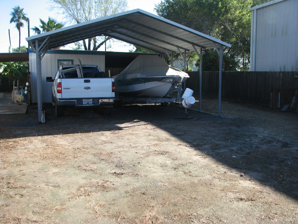 the carport easily accommodates a truck and a trailered boat in front of the truck is the bunk room and to the left in front of the boat is a storage area.