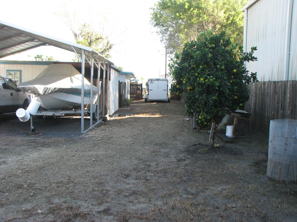 looking from the rear of the property toward the front in front of the travel trailer is the gated front entrance.  notice the orange tree to your right.  there is also a key lime tree where i was standing to take this picture.