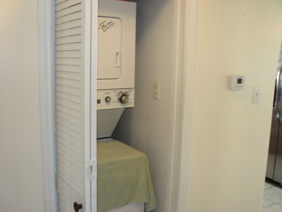 hall closet with stack washer and dryer