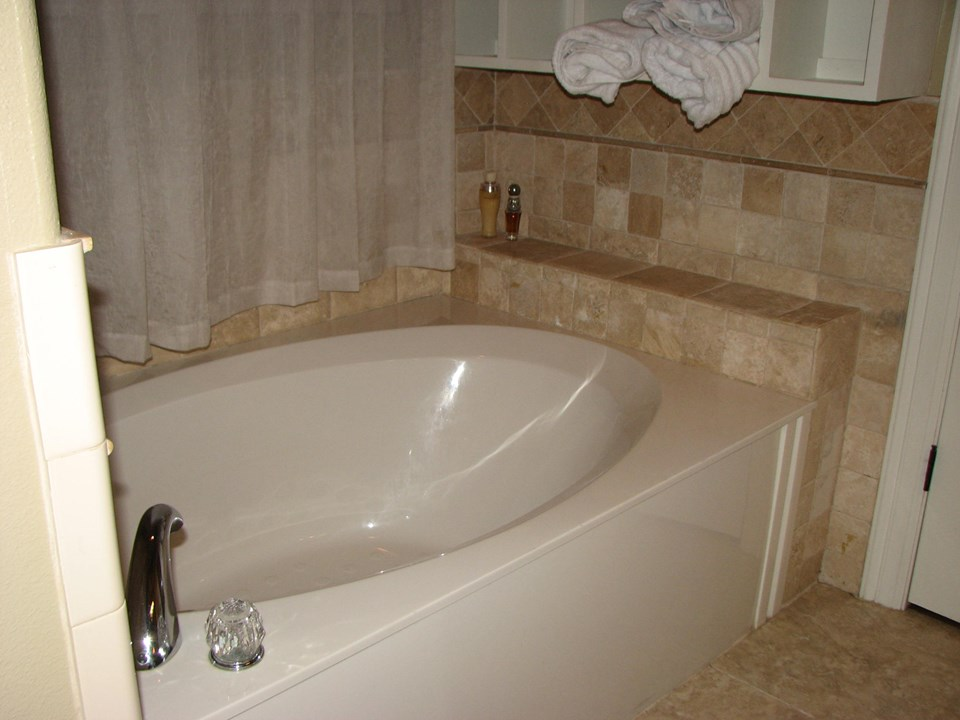 beautiful, inviting soaking tub with towel display/storage on the wall
