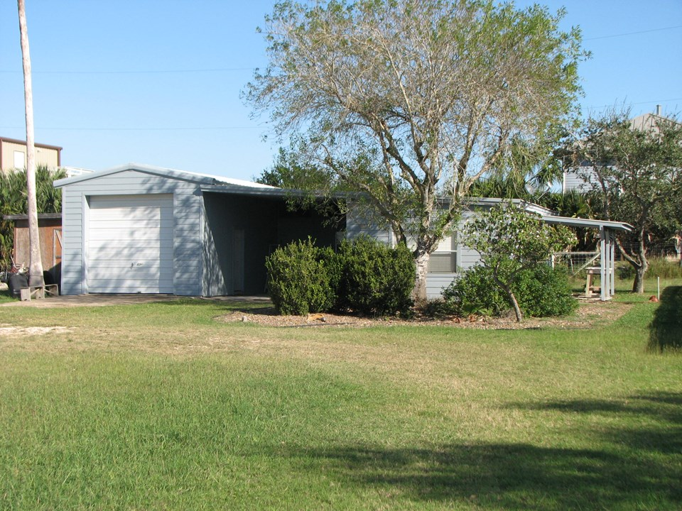 the living quarters are to the right of the carport and the garage is to the left of the carport
