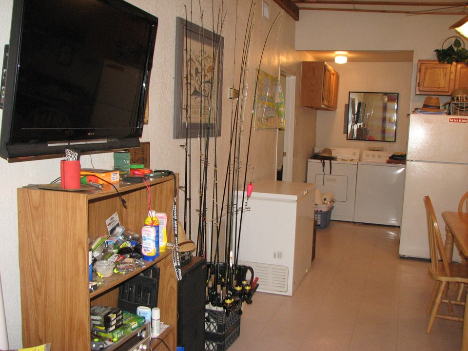 what a great fishing cabin! there is a doorway to the left of the washer and dryer in the background and leads to the bedroom.  there is also a doorway to the right (not shown) that leads to the full bath.