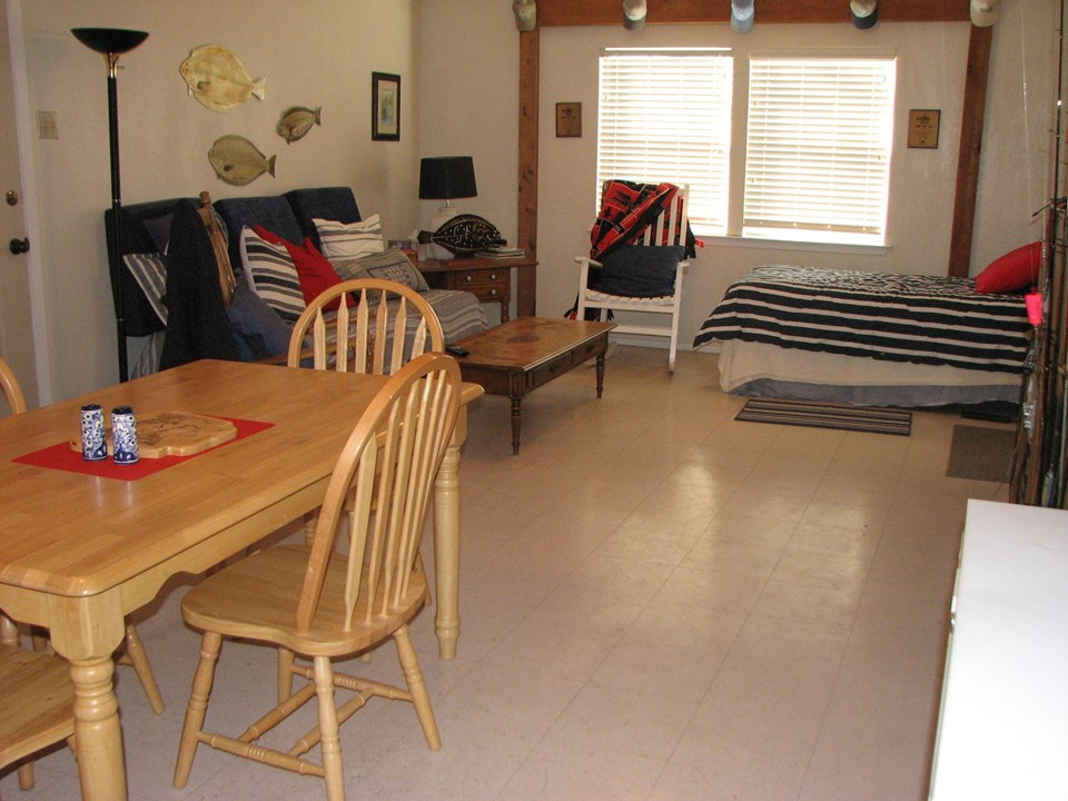 other side of kitchen, living area there is a doorway on your left that leads to the outdoor covered patio that has a fish cleaning table.  the door to the carport is on your right just this side of the twin bed.