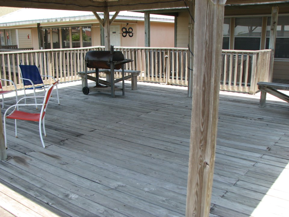 covered deck above the boat slips your can see the front of the home behind the covered deck