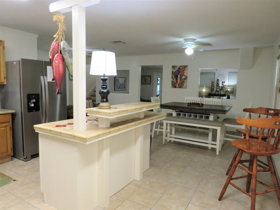 breakfast bar and dining table accommodates many guests the living room is in the center background of this photo.